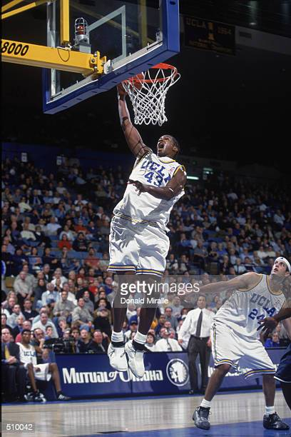 Forward TJ Cummings of the UCLA Bruins jumps to dunk the ball while teammate forward Jason Kapono watches against the Pepperdine Waves during the...