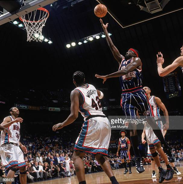 Forward Walt Williams of the Houston Rockets shoots the ball as forward Lorenzen Wright of the Memphis Grizzlies stands underneath the basket during...