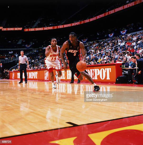 Guard Eddie Jones of the Miami Heat dribbles past guard Emanual Davis of the Atlanta Hawks for a rebound during the NBA game at Phillips Arena in...