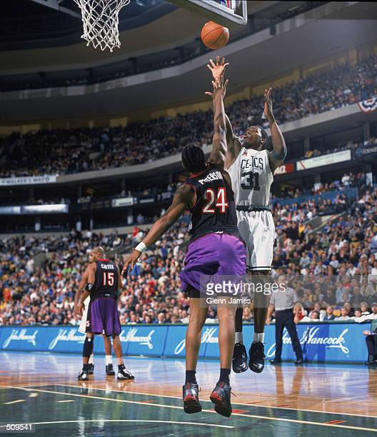 Guard Joe Johnson of the Boston Celtics shoots over forward Morris Peterson of the Toronto Raptors during the NBA game at the FleetCenter in Boston...