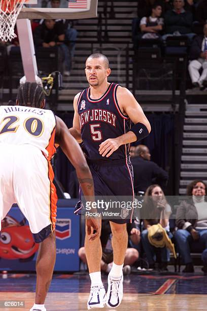 Jason Kidd of the New Jersey Nets dribbles down court as Larry Hughes of the Golden State Warriors guards him at The Arena in Oakland California...