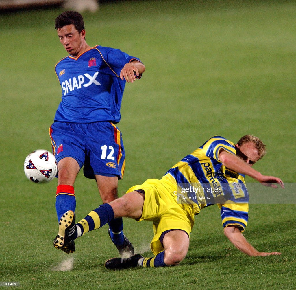 John Hutchinson #12 of the Spirit is tackled by Jon McKain #4 of the Strikers during the NSL round 5 match between the Brisbane Strikers and the Northern Spirit played at Ballymore in Brisbane, Australia. DIGITAL IMAGE. Mandatory Credit: Darren England/ALLSPORT