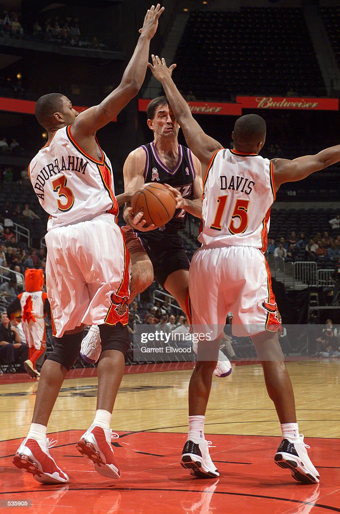 John Stockton #12 of the Utah Jazz splits two defenders against the Atlanta Hawks during a game at Phillips Arena in Atlanta, Georgia.