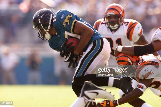 Keenan McCardell of the Jacksonville Jaguars struggles to evade a tackle during the game against the Cincinnati Bengals at Alltell Stadium in...