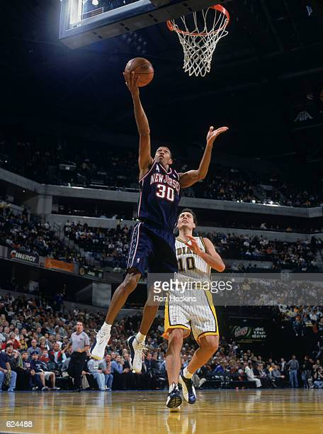 Kerry Kittle of the New Jersey Nets makes a layup as Jeff Foster of the Indiana Pacers looks on during the game at Conseco Fieldhouse in Indianapolis...