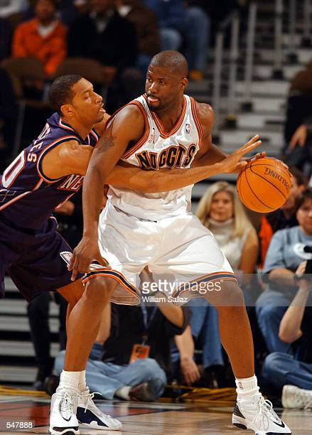 Kerry Kittles of the New Jersey Nets left reaches in on Isaiah Rider of the Denver Nuggets during the NBA game at Pepsi Center in Denver Colorado...