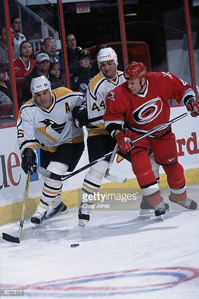 Kevin Stevens of the Pittsburgh Penguins moves for the puck with teammate Stephane Richer and Aaron Ward of the Carolina Hurricanes during the game...