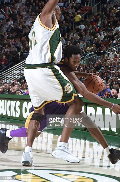 Kobe Bryant of the Los Angeles Lakers squeeks around Vin Baker of the Seattle SuperSonics at Key Arena in Seattle Washington DIGITAL IMAGE Note to...
