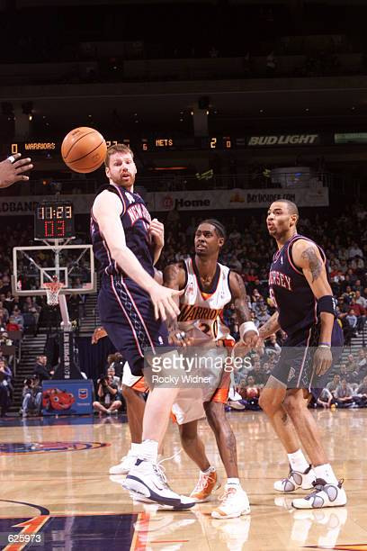 Larry Hughes of the Golden State Warriors passes the ball between Todd MacCulloch and Kenyon Martin of the New Jersey Nets during a game at The Arena...