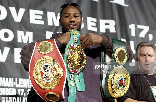 Lennox Lewis shows off his belts during a post fight press conference of the WBC/IBF World Heavyweight Championship fight against Hasim Rahman at the...