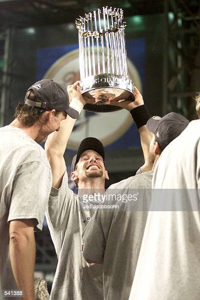 Luis Gonzalez of the Arizona Diamondbacks lifts the trophy after the team won the World Series over the New York Yankees at Bank One Ballpark in...