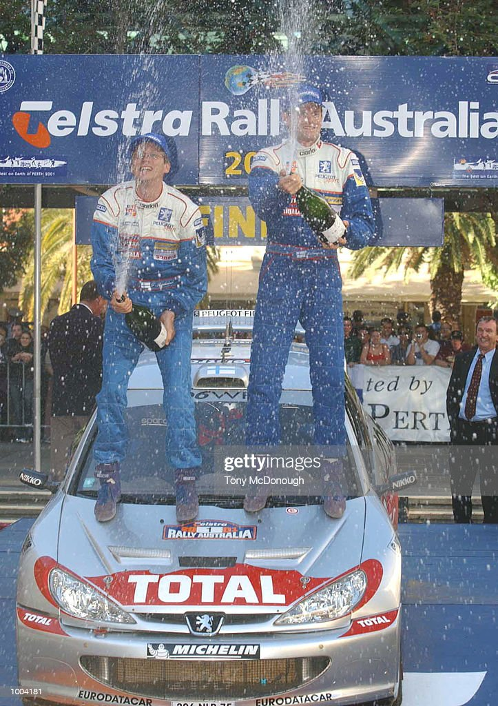 Marcus Gronholm and co-driver Timo Rautiainen celebrate their win of the Telstra Rally Australia 2001 in a Peugeot 206 WRC in Forrest Place, Perth, Australia. DIGITAL IMAGE Mandatory Credit: Tony McDonough/ALLSPORT