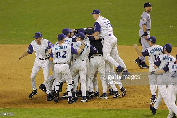 Members of the Arizona Diamondbacks celebrate defeating the New York Yankees to win game 7 to capture the World Series at Bank One Ballpark in...