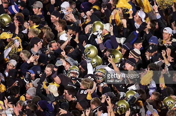 Members of the Colorado Buffaloes celebrate with fans swarming them at the center of the field after upsetting the Nebraska Cornhuskers 6236 at...