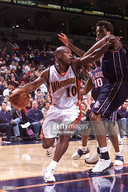 Mookie Blaylock of the Golden State Warriors dribbles around the New Jersey Nets defense while looking for the open man during a game at The Arena in...