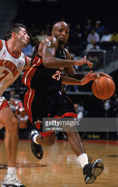 Point guard Anthony Carter of the Miami Heat dribbles the ball past forward Toni Kukoc of the Atlanta Hawks during the NBA game at Phillips Arena in...