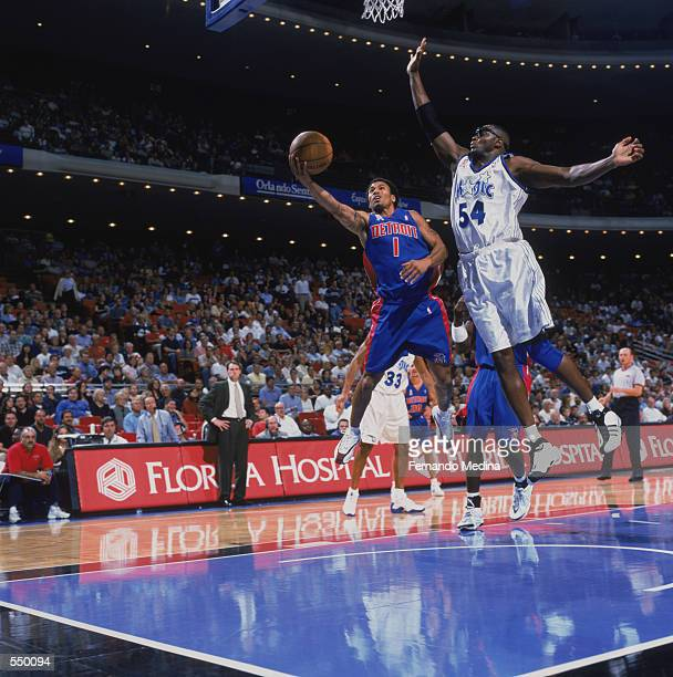 Point guard Dana Barros of the Detroit Pistons shoots past forward Horace Grant of the Orlando Magic during the NBA game at TD Waterhouse Centre in...