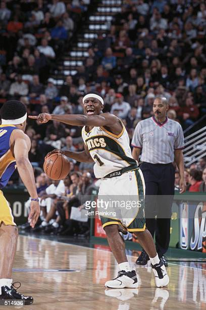 Point guard Shammond Williams of the Seattle SuperSonics signals a play as point guard Derek Fisher of the Seattle SuperSonics plays defense during...