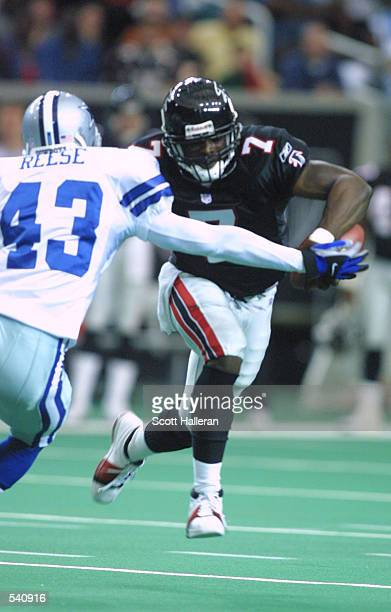 Quarterback Michael Vick of the Atlanta Falcons tries to scramble past defender Izell Reese of the Dallas Cowboy in the Georgia Dome in Atlanta,...