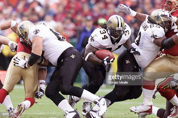 Ricky Williams of the New Orleans Saints runs through the blocks of his teammates against the the San Fransisco 49ers defense during the game at 3...