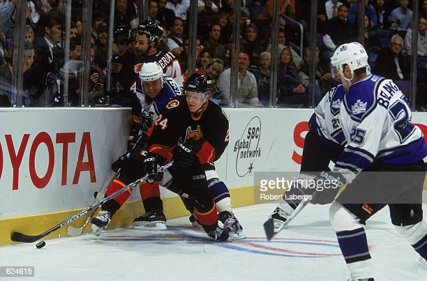 Right wing Jukka Hentunen of the Calgary Flames and Mattias Norstrom of the Los Angeles Kings fight for the puck during a hockey match at the Staples...