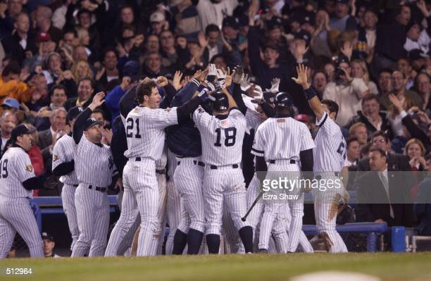 Scott Brosius of the New York Yankees is congratulated by his teammates as he heads into the dugout after hitting a two run home run against the...