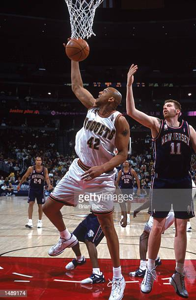 Scott Williams of the Denver Nuggets leaps for the basket as Todd MacCulloch of the New Jersey Nets looks on during the game at Pepsi Center in...