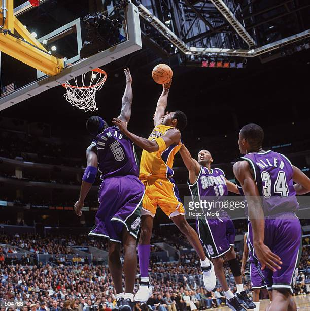 Small guard Kobe Bryant of the Los Angeles Lakers dunks the ball as forward Tim Thomas of the Milwaukee Bucks tries to block during the NBA game...