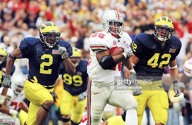 Tailback Jonathan Wells of Ohio State runs for his second touchdown past Cato June and John Spytek of Michigan at Michigan Stadium in Ann Arbor...