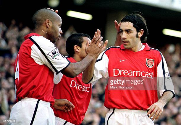 Thierry Henry of Arsenal is congratulated by team mate Robert Pires after opening the scoring during the FA Barclaycard Premiership match between...