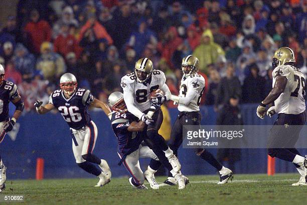 Willie Jackson of the New Orleans Saints tries to shake a tackle by Ty Law of the New England Patriots during the game at Foxboro Stadium in Foxboro...