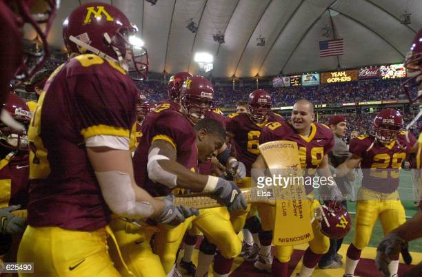 The Minnesota Gophers grab Paul Bunyan's Axe from the Wisconsin bench after they beat the Badgers 4231 at the Hubert H Humphrey Metrodome in...