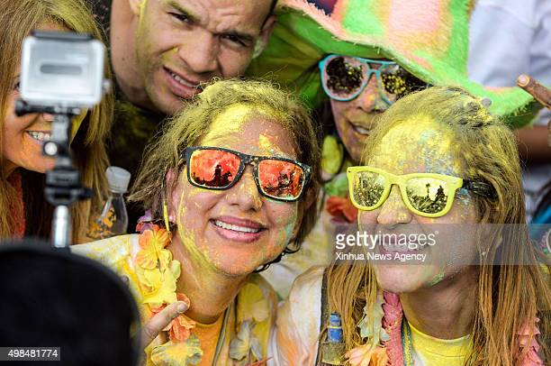 People take part in the Color Run in Caracas Venezuela on Nov 22 2015 The event is a 5km family race that celebrates the health the hapiness and the...