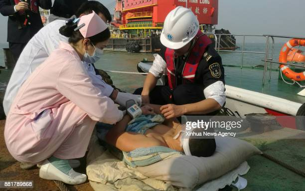 GUANGZHOU Nov 28 2017 Medical personnel treat a crew member rescued from a cargo ship that sank off the coast of south China's Guangdong Province Nov...