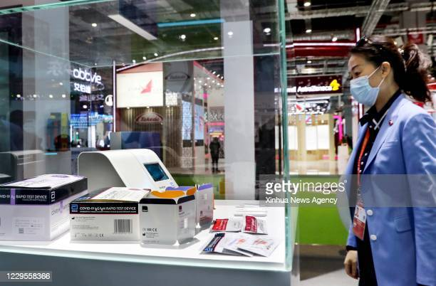 Nov. 5, 2020 -- A visitor views COVID-19 rapid test device showcased by Abbott Laboratories at the special area for public health and epidemic...