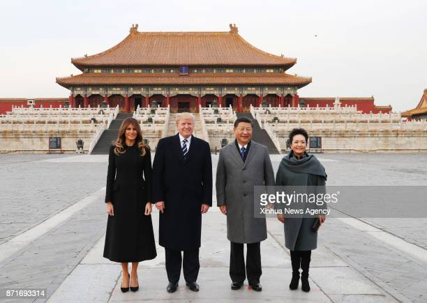 Chinese President Xi Jinping and his wife Peng Liyuan and US President Donald Trump and his wife Melania Trump pose for a photo in front of Taihedian...