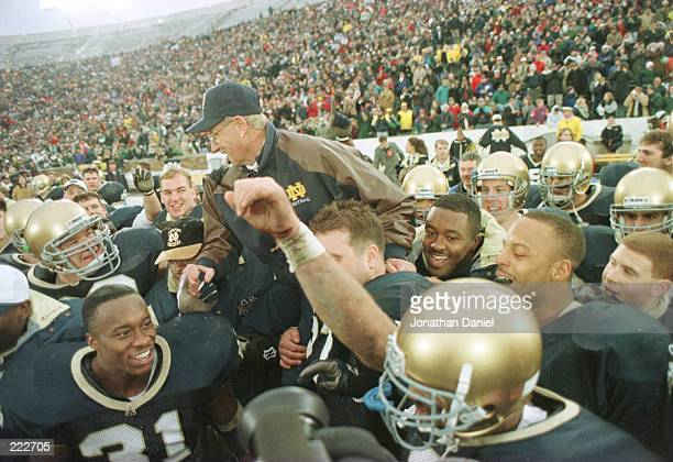 Head coach Lou Holtz of the Notre Dame Fighting Irish is carried off the field by his team after defeating the Rutgers Scarlet Knights 62-0 at Notre...