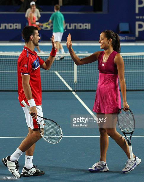 Novak Djokovic and Ana Ivanovic of Serbia celebrate winning a point during their mixed doubles match against Andrey Golubev and Yaroslava Shvedova of...