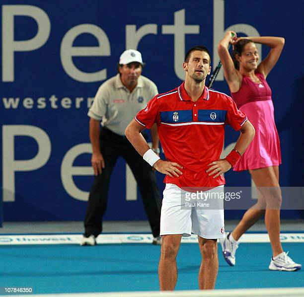 Novak Djokovic and Ana Ivanovic of Serbia look on after dropping a point during their mixed doubles match against Andrey Golubev and Yaroslava...