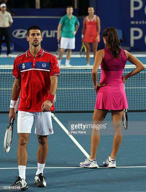 Novak Djokovic and Ana Ivanovic of Serbia look on while waiting for a review during their mixed doubles match against Andrey Golubev and Yaroslava...