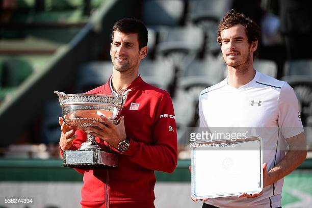 Novak Djokovic celebrates victory with trophy and Andy Murray during the day fifteen of the French Open 2016 at Roland Garros on June 5 2016 in Paris...