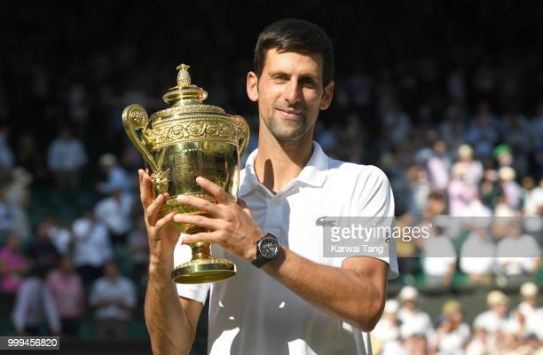 Novak Djokovic celebrates with the trophy after winning the men's singles final on day thirteen of the Wimbledon Tennis Championships at the All...