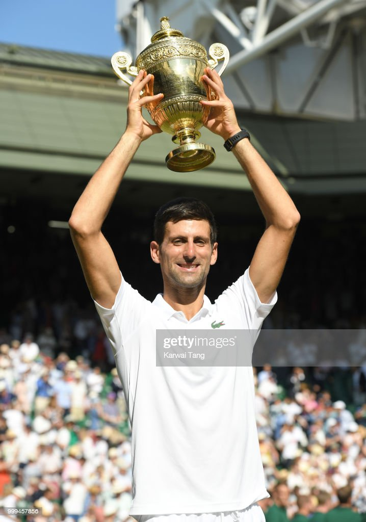Novak Djokovic celebrates with the trophy after winning the men's singles final on day thirteen of the Wimbledon Tennis Championships at the All England Lawn Tennis and Croquet Club on July 15, 2018 in London, England.