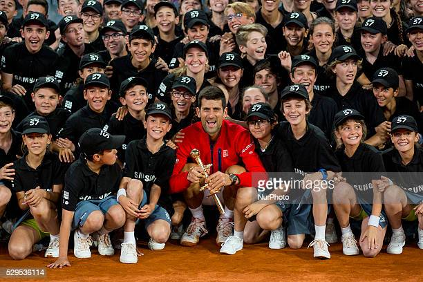 Novak Djokovic from Serbia poses for photographers with the madrid mutua volunteers with his trophy after winning his Madrid Open tennis tournament...
