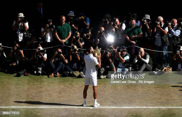 Novak Djokovic holds the trophy after winning the Gentlemen's Single Final against Kevin Anderson on day thirteen of the Wimbledon Championships at...