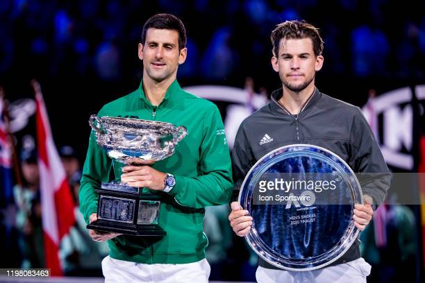 Novak Djokovic of Serbia and Dominic Thiem of Austria hold their trophies after the completion of the finals of the 2020 Australian Open on February...