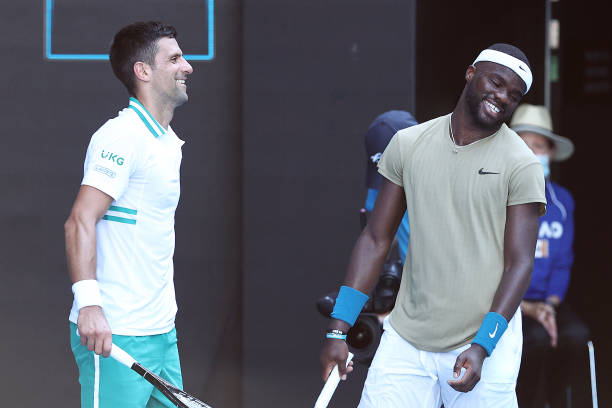 Novak Djokovic of Serbia and Frances Tiafoe of the United States share a laugh in their Men's Singles second round match during day three of the 2021...
