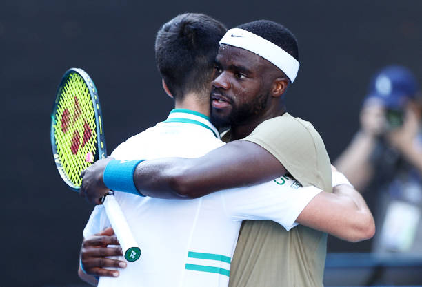 Novak Djokovic of Serbia and Frances Tiafoe of the United States embrace at the net following their Men's Singles second round match during day three...