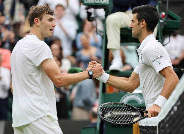 Novak Djokovic of Serbia and Jack Draper of Great Britain shake hands at the net after their Men's Singles First Round match during Day One of The...