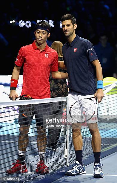 Novak Djokovic of Serbia and Kei Nishikori of Japan line up before their men's singles semi final on day seven of the ATP World Tour Finals at O2...